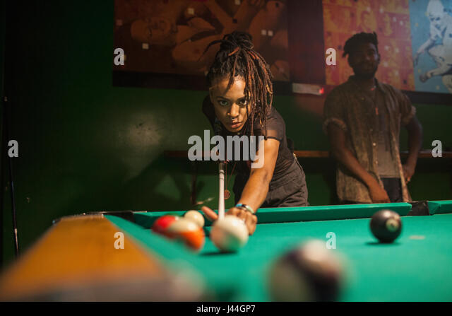 A young woman playing pool. - Stock Image