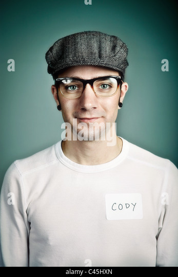 A hip yet friendly young man wearing a cap and plastic glasses with a name badge. He has an alternative look with - Stock Image