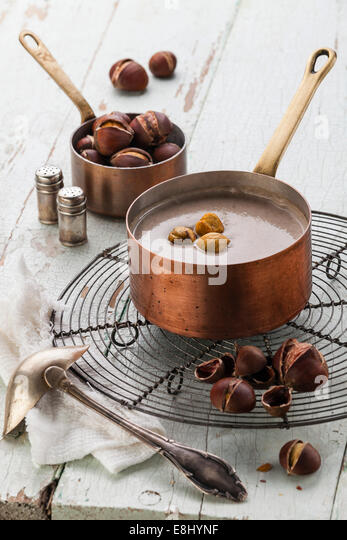 Chestnut soup in copper pot with roasted chestnuts on blue textural background - Stock Image