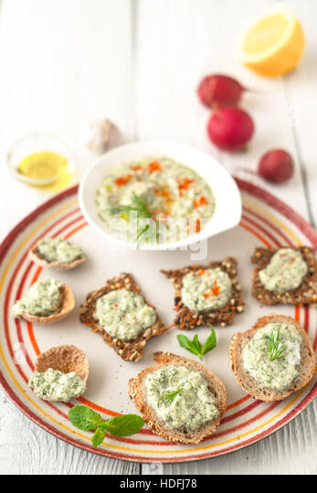 Colorful plate with different bread with tzatziki on the white table - Stock Image