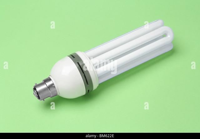 Energy saving lightbulb on green background - Stock Image