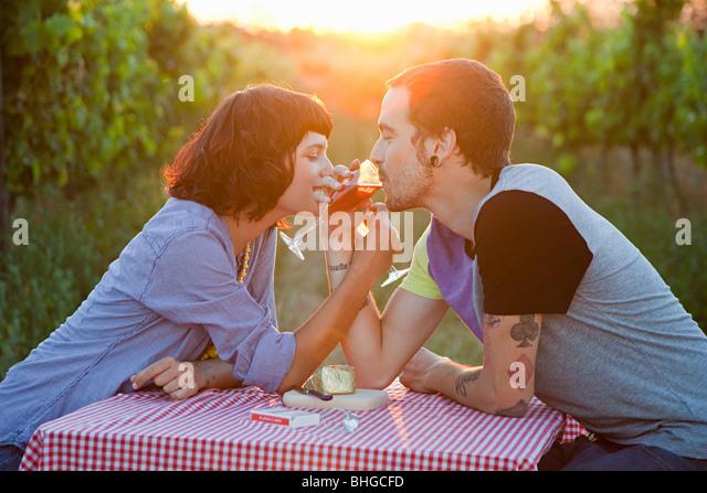 Couple drinking wine in a field - Stock-Bilder