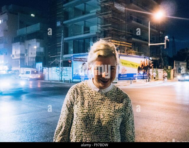 Portrait Of Smiling Woman Standing On Illuminated Street - Stock Image
