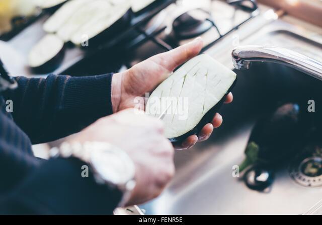 Mans hands making cuts on aubergine halves in kitchen - Stock Image
