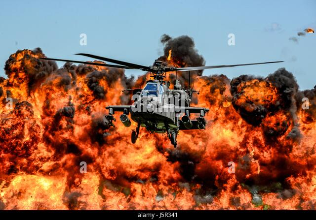 A U.S. Army AH-64D Apache attack helicopter flies in front of a wall of fire during the South Carolina National - Stock Image