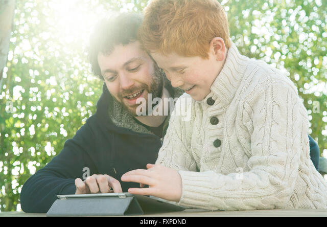 Father and son looking at digital tablet together - Stock Image