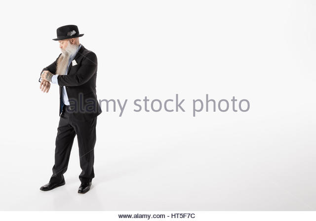 Hipster businessman with beard checking the time on wristwatch against white background - Stock-Bilder