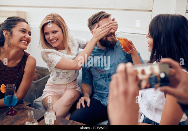 Young people sitting together enjoying party. Woman closing eyes of a man with another giving drink. Young friends - Stock Image