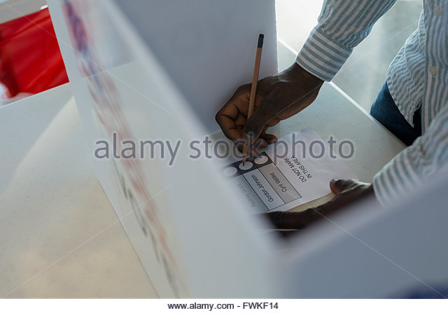 Voter in voting booth - Stock Image