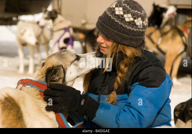 Canadian winter sports dogsledding woman hugs sled dog outdoors in snow, Banff Canada - Stock Image