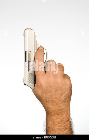Close up of hand holding a gun - Stock Image