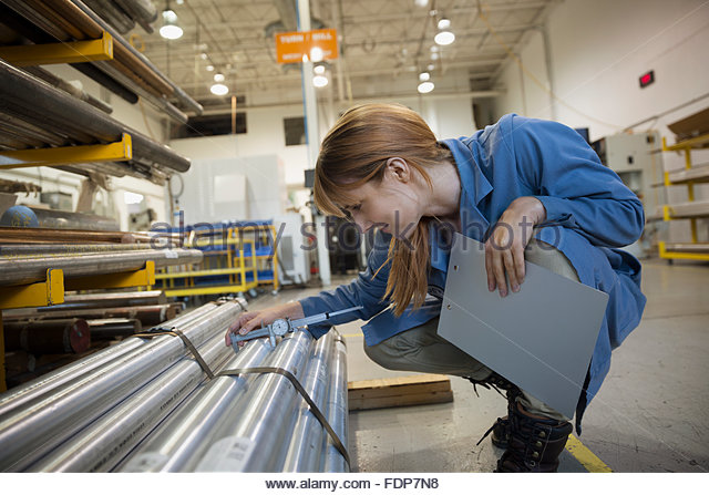 Worker examining parts in factory - Stock Image