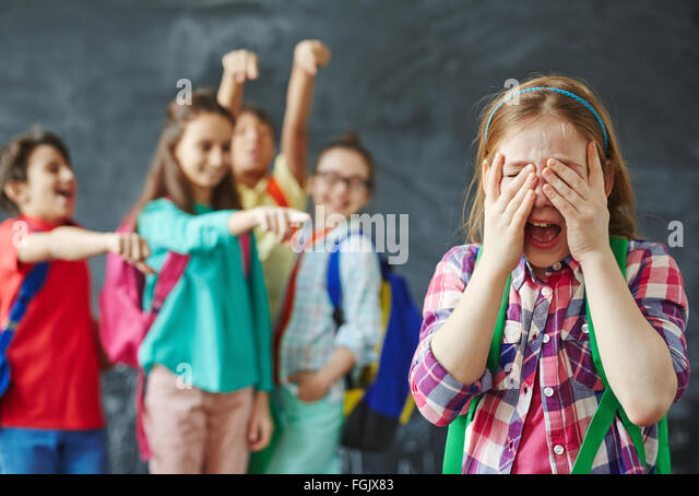 Schoolgirl crying on background of teasing classmates - Stock Image