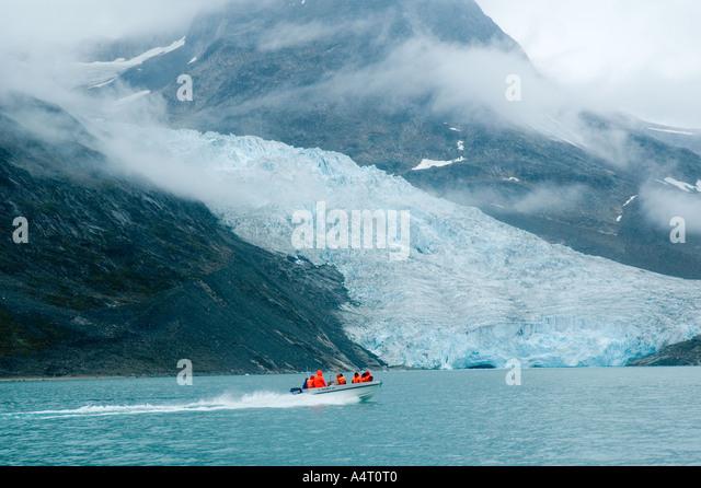 Open boat passing the Apusêrajik glacier, Ikâsaulaq Fjord, East Greenland - Stock Image