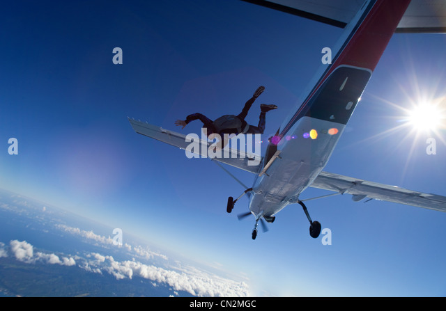 Skydiver jumping from plane over north shore of Oahu, Hawaii - Stock Image