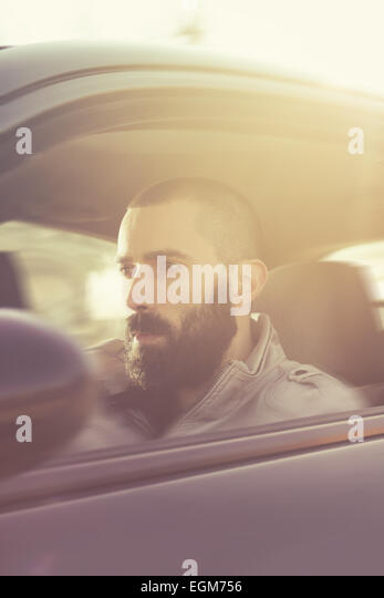 Young handsome man driving his car on a beautiful sunny day. Retro tones. Motion blur - Stock-Bilder