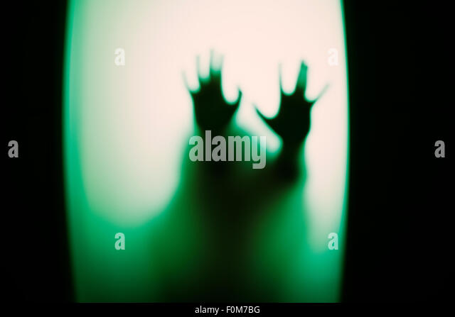 Silhouette of little child holding up hands. Conceptual image of childhood fears, abuse and safety of children. - Stock Image