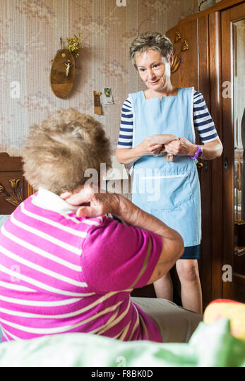 Home care aid assisting elderly woman, Dordogne, France. - Stock Image