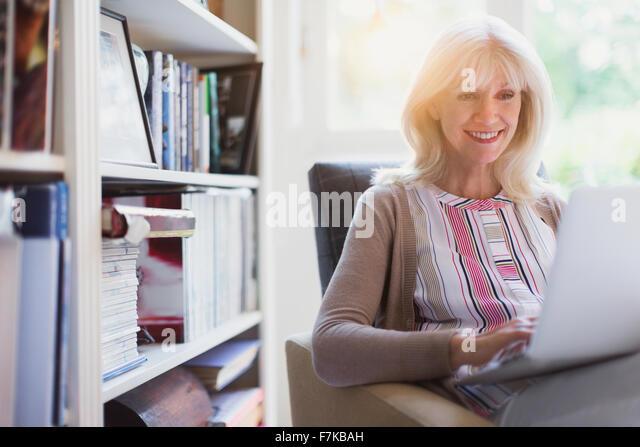Smiling senior woman using laptop in den - Stock Image