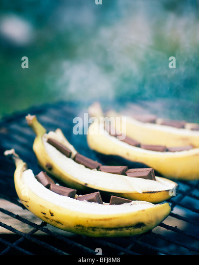 Bananas with chocolate on a barbecue, Sweden. - Stock-Bilder