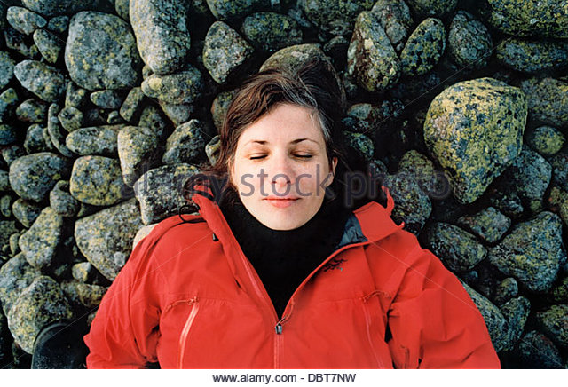 Woman lying on rocks - Stock Image