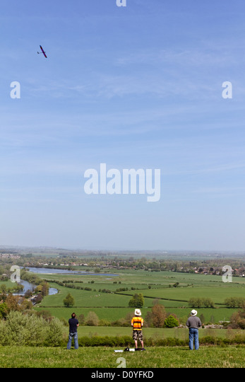Three men and a remote control glider on a sunny day in Oxfordshire, England - Stock Image