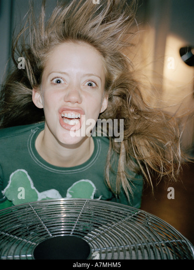 A woman making a crazy face above a fan - Stock Image