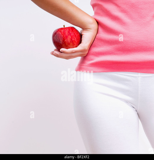 Mid section view of a woman holding an apple - Stock-Bilder