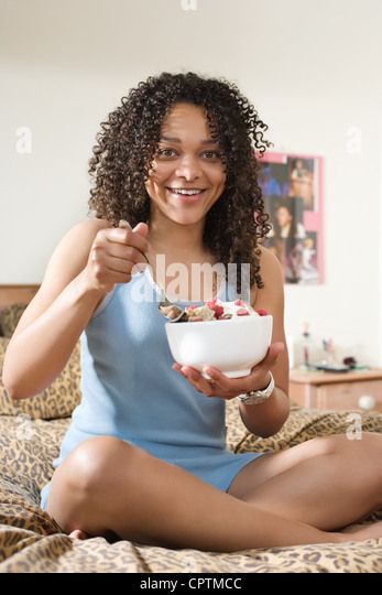 Young woman eating cereal yogurt and raspberry's from a breakfast bowl - Stock Image