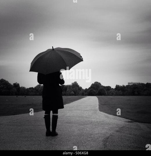 A women stands in Hyde Park on a rainy day. London, England UK. - Stock-Bilder