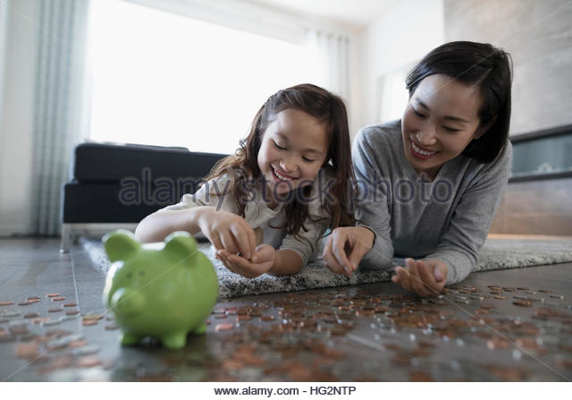 Mother and daughter counting and depositing coins into piggy bank on living room floor - Stock Image