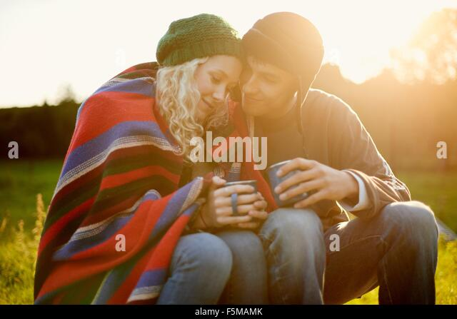 Romantic young camping couple wrapped in blanket with tea drinks - Stock Image