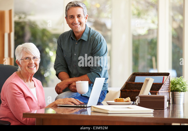 Adult Son Helping Mother With Laptop - Stock Image