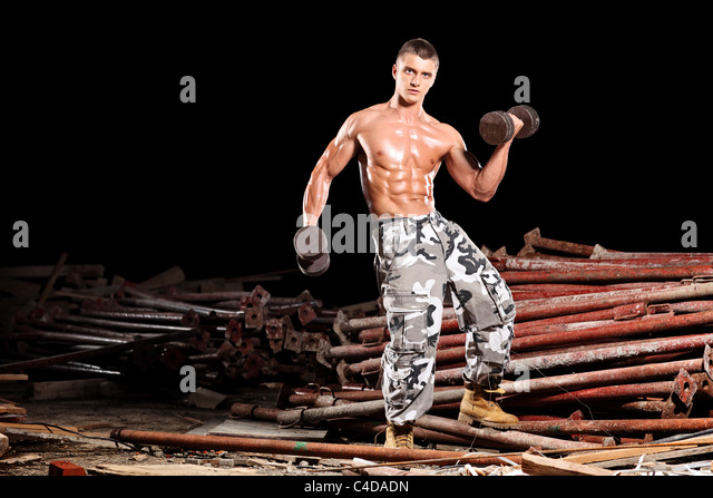 A body builder exercising with weights outside - Stock Image