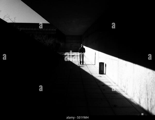 Single person standing in alley of light - Stock Image