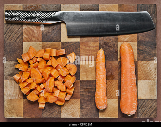 Chopped Carrots on Chopping Board with Knife - Stock Image