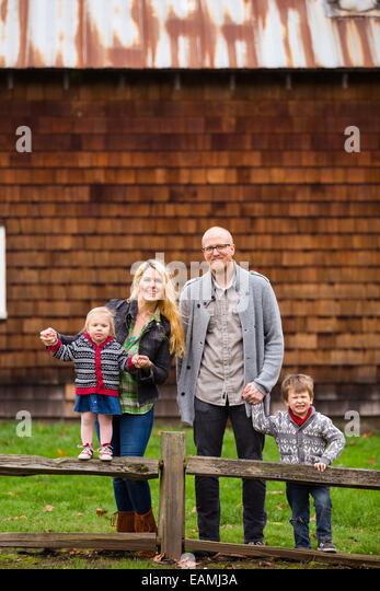 Family lifestyle portrait of a mother, father, son and daughter in front of a rustic barn in the country. - Stock-Bilder