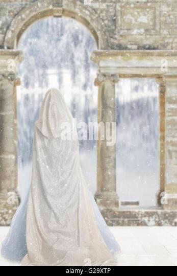 cloaked woman by castle lake - Stock-Bilder