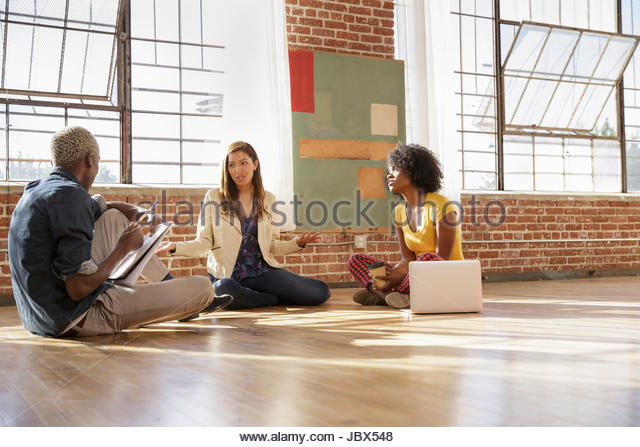 Three colleagues sitting on floor in new office space, having discussion - Stock-Bilder