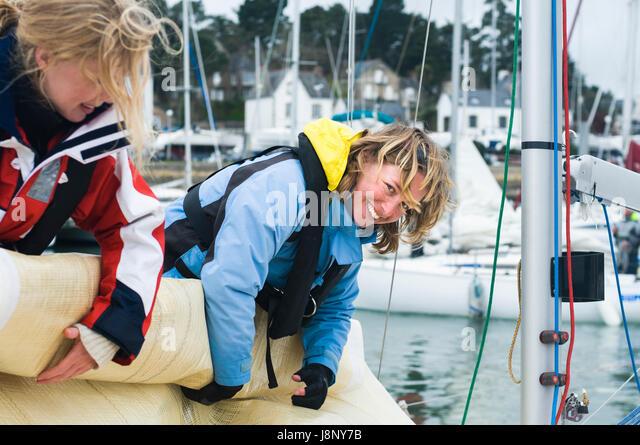 Women rolling up sail on sailboat - Stock-Bilder