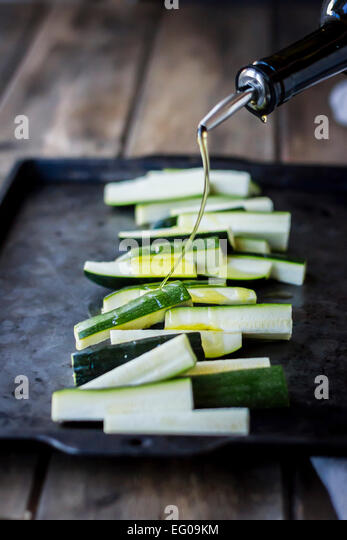 Zucchini on a baking tray with olive oil - Stock Image