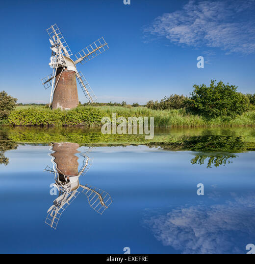 Turf Fen Winmill reflecting in the smooth waters of the Norfolk Broads, Norfolk, England - Stock Image