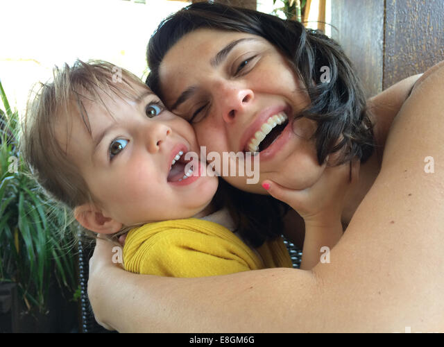Mother and daughter (18-23 months) embracing and laughing - Stock Image