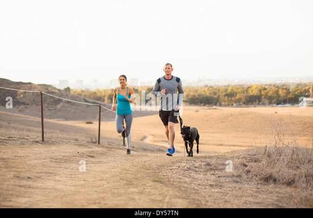 Couple running with dog - Stock Image