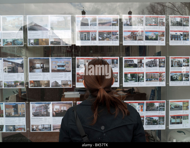 Woman looking at houses for sale in estate agents window in Utrecht The Netherlands - Stock-Bilder