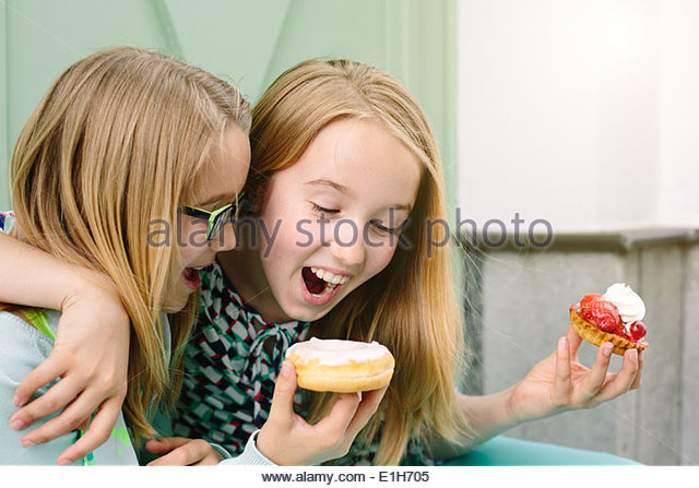Two happy sisters holding cakes - Stock Image
