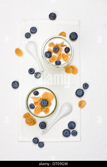 Two portions of yogurt with cornflakes and berries - Stock Image