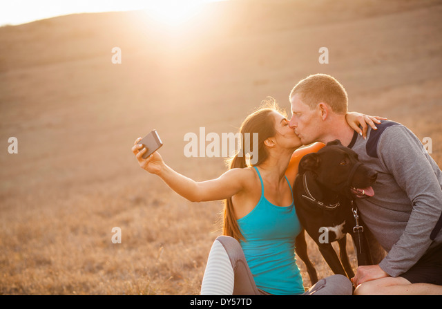 Kissing couple with dog - Stock Image