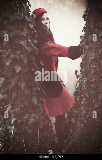 a woman with a red coat and hat between two trunks - Stock Image