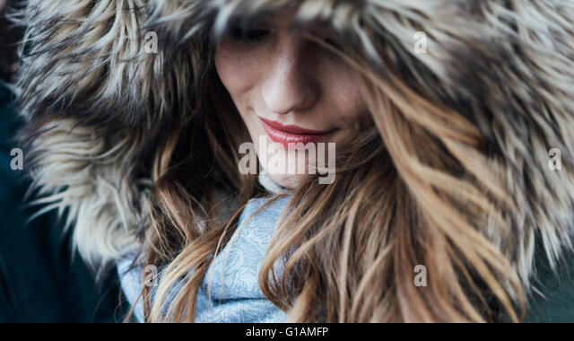 Young smiling woman with fur hood, fashion and winter concept - Stock-Bilder